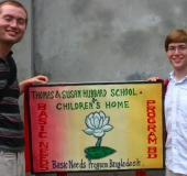 Richard and Chandler Hubbard posing in front of the Susan Hubbard School sign